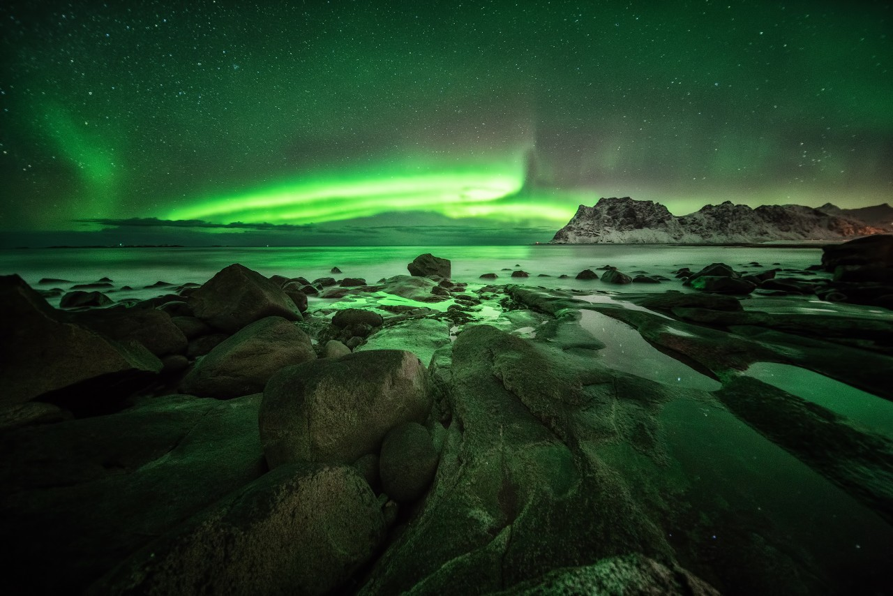Polar light photo on the Lofoten in Norway, Uttakleiv, with a wide angle lens and stones in the foreground