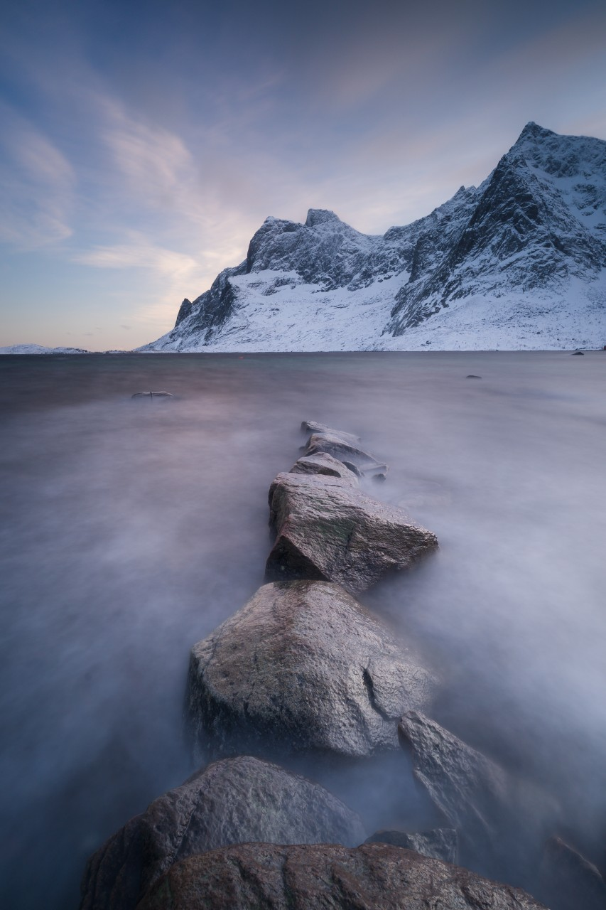 Long time exposure in Norway with rocks in the foreground and mountains in the background.