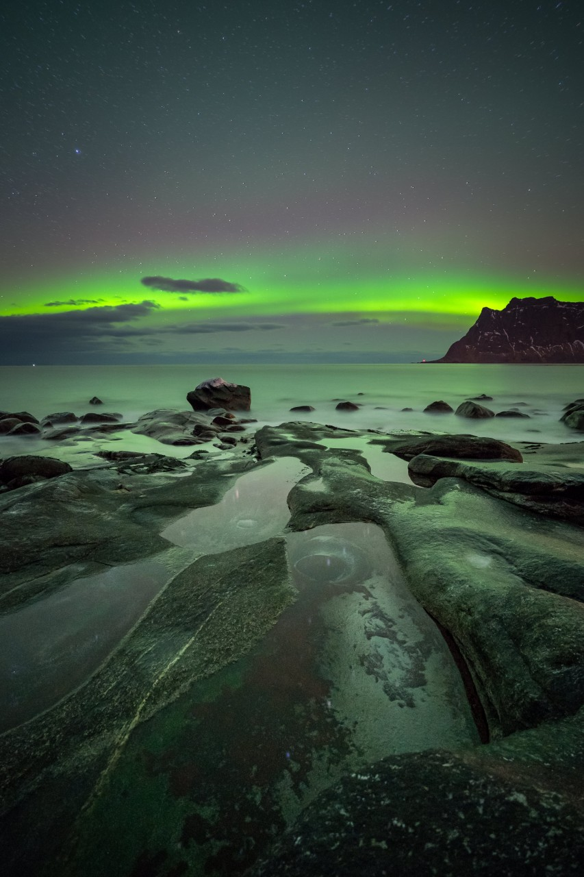Northern lights with many rocks in the foreground